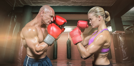 fighting stance: Side view of boxers with fighting stance against red boxing area with punching bags