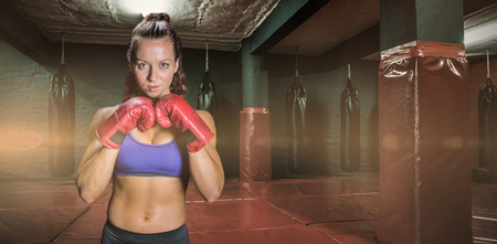 fighting stance: Portrait of pretty woman with fighting stance against red boxing area with punching bags