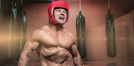 headgear: Angry boxer with headgear against punching bags in red boxing area Stock Photo