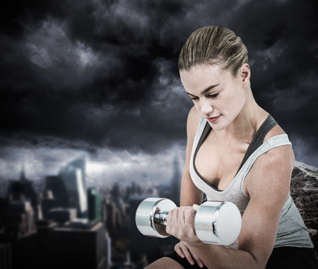 dark city: Muscular woman working out with dumbbells  against large rock overlooking dark city Muscular woman working out with dumbbells on white background