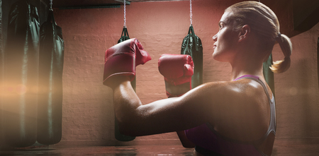 fighting stance: Side view of female boxer with fighting stance against punching bags in red boxing area