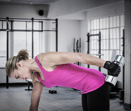weightlifting gloves: Muscular woman exercising with dumbbells  against interior of a gym