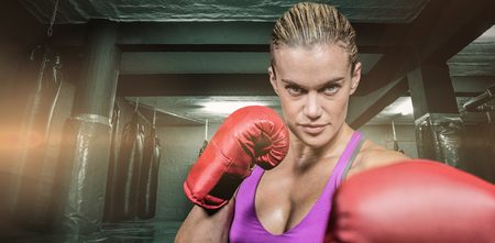 Portrait of female boxer with fighting stance against red boxing area with punching bags Stock Photo