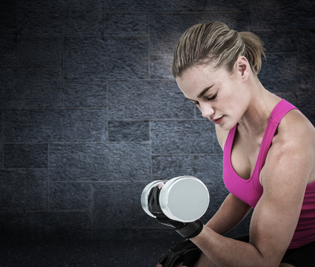 weightlifting gloves: Muscular woman exercising with dumbbells  against grey Stock Photo