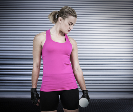 weightlifting gloves: Muscular woman exercising with dumbbells  against shutter in gym