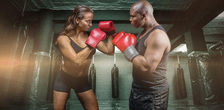 fighting stance: Male and female boxer with fighting stance against red boxing area with punching bags