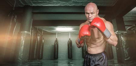 boxeador: Retrato del boxeador con guantes de boxeo contra el área roja con sacos de boxeo