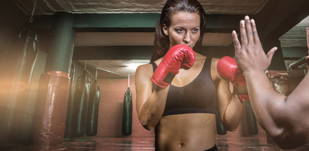 fighting stance: Female boxer with fighting stance against trainer hand against red boxing area with punching bags