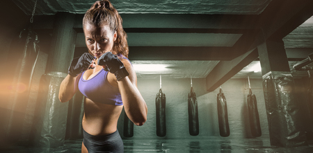 fighting stance: Portrait of woman with fighting stance against red boxing area with punching bags