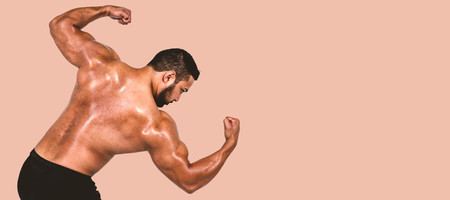 flexing: Muscular man flexing for camera against orange background Stock Photo