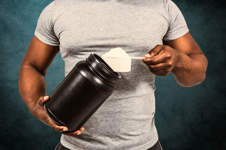 scooping: Fit man scooping protein powder  against blue background
