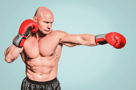 shaved head: Bald boxer in fighting stance against green background