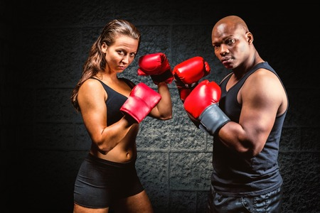 fighting stance: Portrait of male and female athletes with fighting stance against dark background Portrait of male and female athletes with fighting stance against black background