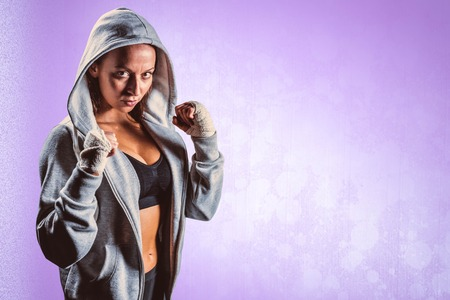 fighting stance: Portrait of female boxer in hood with fighting stance against purple background