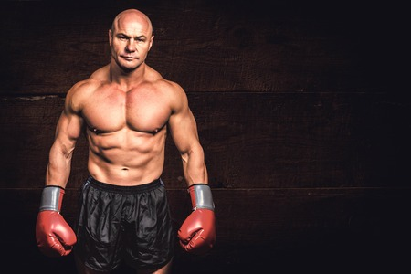 shaved head: Portrait of bald man with boxing gloves against black wood Stock Photo