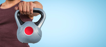 mid section: Mid section of a muscular man holding a kettlebell against blue background