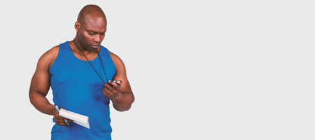 adult  body writing: Fit trainer checking his stopwatch against grey background Stock Photo