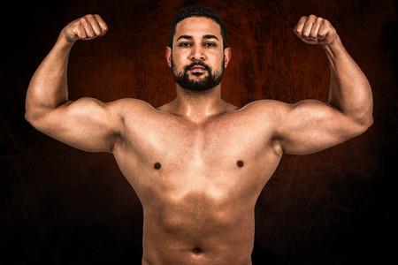 flexing: Muscular man flexing for camera against dark background