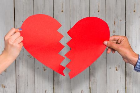 broken relationship: Two hands holding broken heart against wooden background Stock Photo