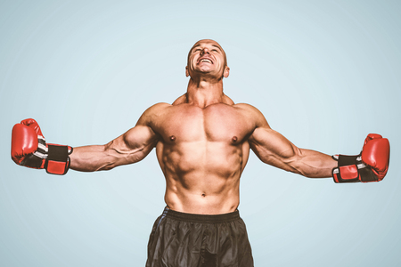 Boxer with arms outstretched against blue background