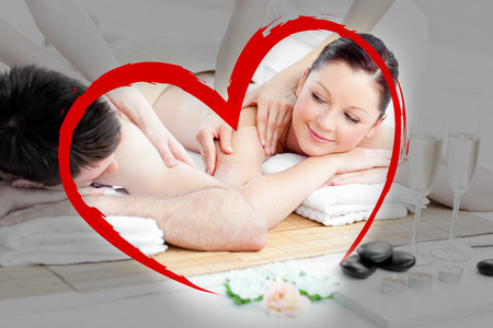 Relaxing young couple enjoying a back massage against heart photo