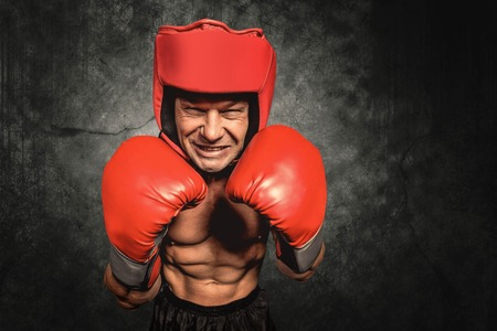 headgear: Angry boxer with gloves and headgear against dark background