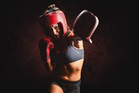 mottled: Female boxer with gloves and headgear punching against dark background Stock Photo