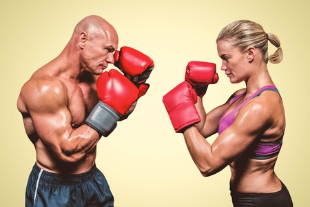 Side view of boxers with fighting stance against yellow background