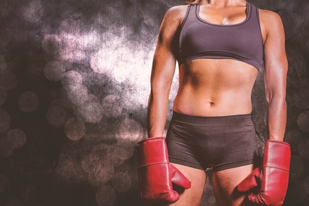 female boxer: Midsection of female boxer with gloves against glowing background Stock Photo