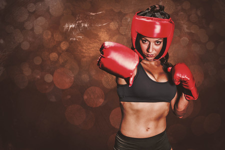 mottled: Portrait of pretty boxer with fighting stance against dark background