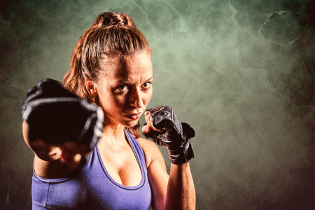 Portrait of female fighter punching against dark background