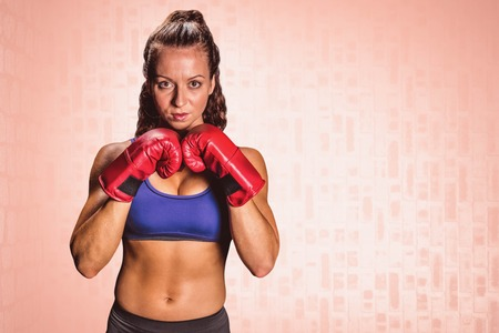 fighting stance: Portrait of pretty woman with fighting stance against pink background Stock Photo