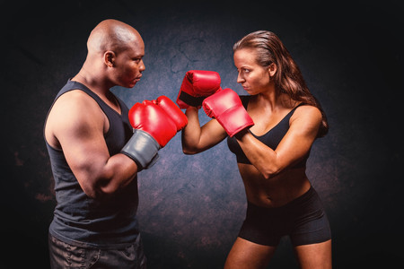 fighting stance: Male and female boxer with fighting stance against dark background Stock Photo