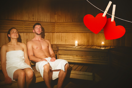 sauna: Couple together in the sauna against hearts hanging on line