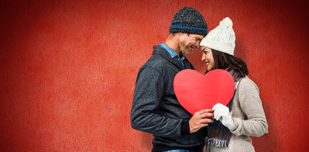 warm clothing: Festive couple in winter clothes against red background Stock Photo