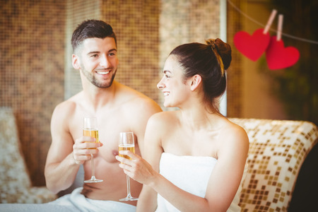 heart suite: Romantic couple together with champagne glasses against hearts hanging on a line Stock Photo