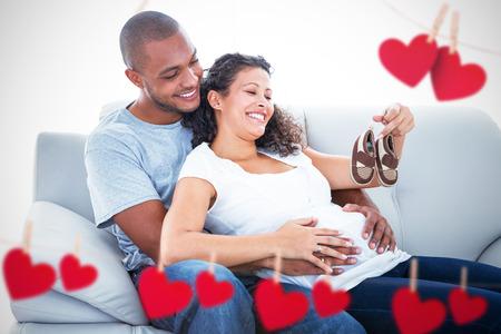 vientre femenino: Pares con los zapatos de bebé contra el corazón colgando de una línea