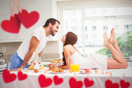 desayuno romantico: Young couple having a romantic breakfast against hearts hanging on a line