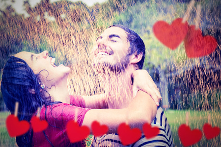fashionable couple: Cute couple hugging under the rain against hearts hanging on a line Stock Photo