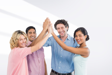 casual business man: Casual business team high fiving against grey vignette