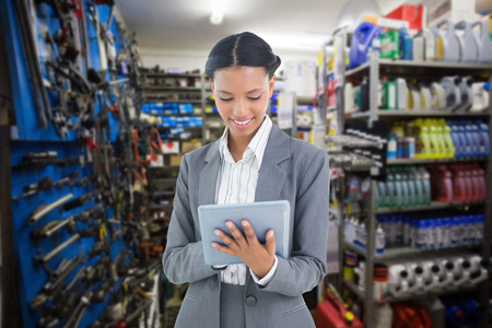 african american woman business: Businesswoman using a tablet with colleagues behind against full store room