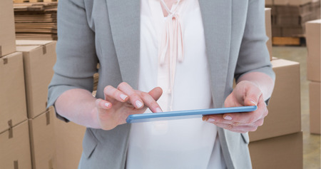 dispatch: Close up of woman using tablet against preparation of goods for dispatch