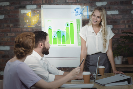 Global business interface against businesswoman briefing over conference table