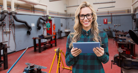 factory interior: Pretty blonde with tablet against factory interior
