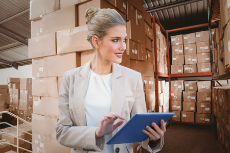 Cheerful stylish businesswoman using digital tablet against shelves with boxes in warehouse