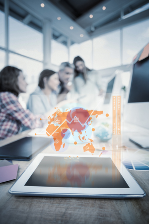 mid adult men: Futuristic interface with the world map  against tablet in the foreground with business people in the background Stock Photo