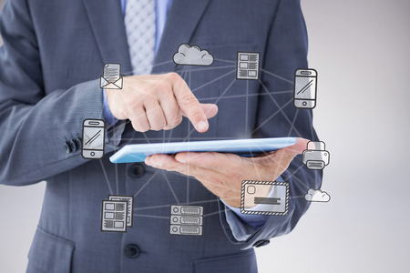 using tablet: Businessman using tablet pc against grey background Stock Photo