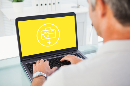 grey hair: Man with grey hair typing on laptop against photography apps Stock Photo