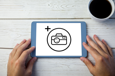 using tablet: Photography apps against hands using tablet on desk Stock Photo