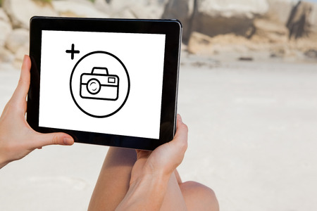 using tablet: Woman sitting on beach using tablet pc against photography apps Stock Photo